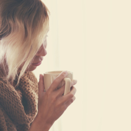 girl with blonde hair wearing a tan sweater and holding a mug