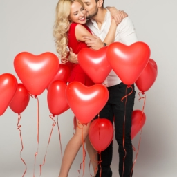 kissing couple posing on grey background with balloons heart. valentine's day.